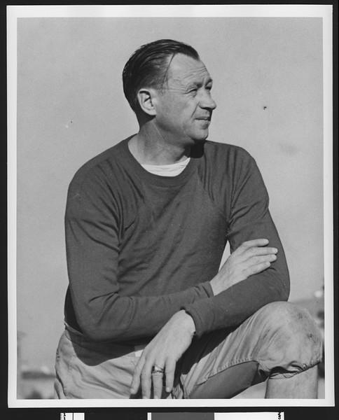 University of Southern California head football coach Jeff Cravath, on one knee, hands folded across torso, wearing a dark sweatshirt. Bovard Field. 1947.