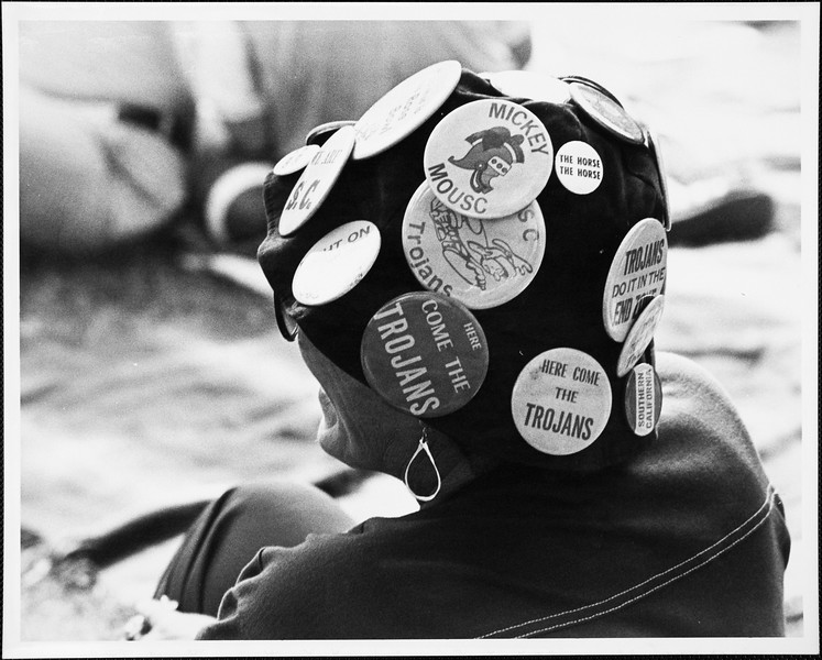 Trojan fan wearing a hat covered with USC buttons, [s.d.]