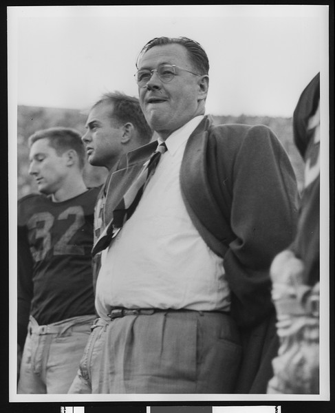 University of Southern California football coach Jeff Cravath on the sidelines at the Los Angeles Coliseum, player #32 (Jay Roundy) to his left, circa 1947-1949.