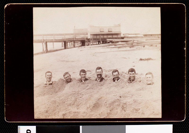 Professor and students of USC buried in sand at a beach, 1889.