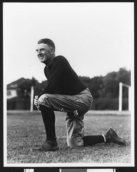 University of Southern California assistant football coach Sam Barry, in dark sweatshirt and on one knee, on Bovard Field, USC campus, 1929.