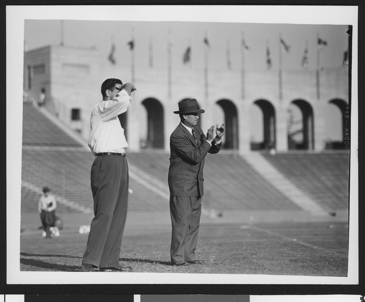 University of Southern California head football coach Jess Hill (right) clapping his hands at a football pre-game practice at the Los Angeles Memorial Coliseum, 1951.