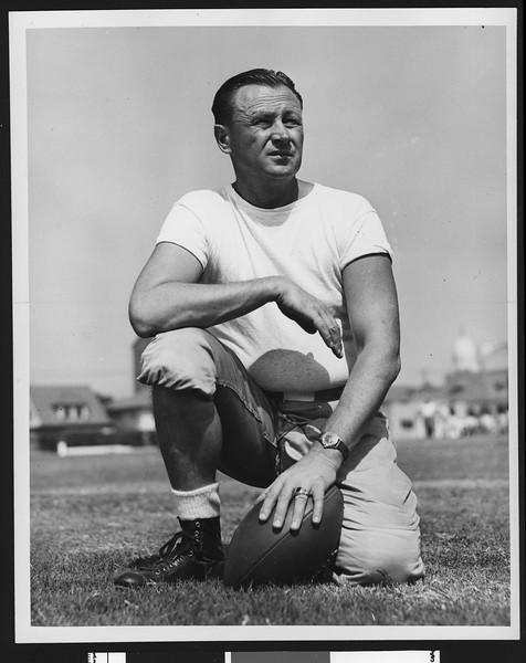 University of Southern California head football coach Jeff Cravath, wearing a white t-shirt, standing on one knee, resting hand on football on ground, Bovard Field. 1946.