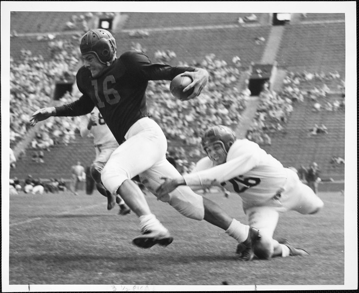 Frank Gifford freeing himself from tackling Johnny Williams in the final spring practice game, 1957