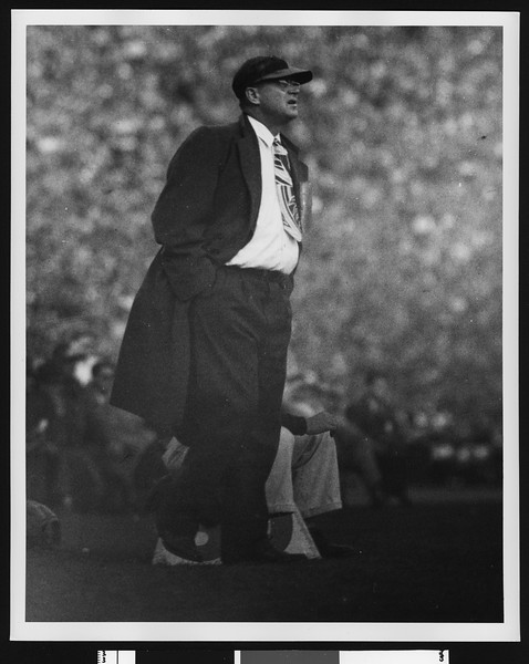 University of Southern California football coach Jeff Cravath pacing the sidelines at a game, wearing a brimmed cap, location Los Angeles?, circa mid-1940s.