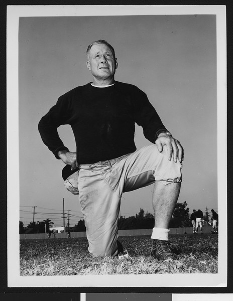 "University of Southern California assistant football coach Roy ""Bullet"" Baker, on one knee, dark sweatshirt, holding cap in hand, Bovard Field, 1949."