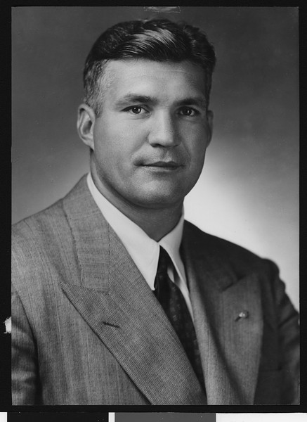 University of Southern California assistant football coach Ray George, studio shot, dark tie with small squares, tweed jacket, 1946.
