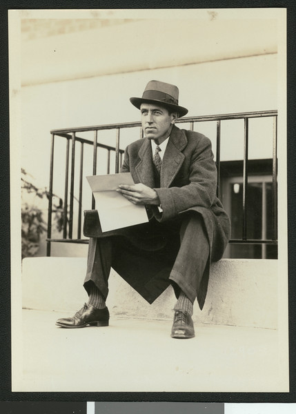 University of Southern California assistant football coach Aubrey Devine, seated outdoors, location unknown, 1931.