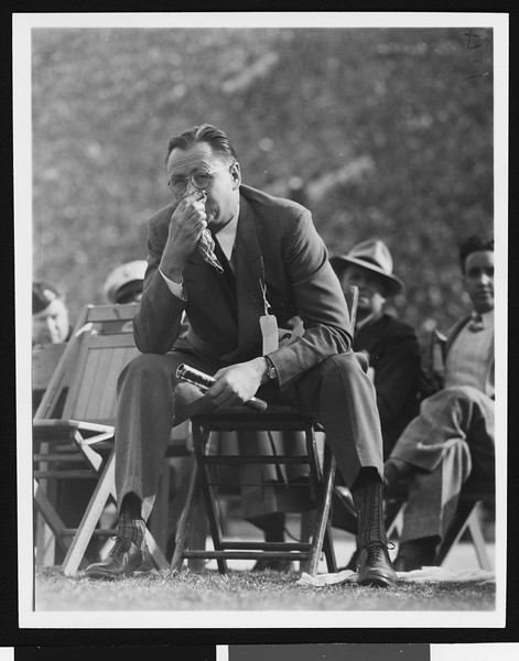 University of Southern California head football coach Jeff Cravath at the UCLA-USC game, sitting in a wooden chair on the sidelines blowing his nose, Los Angeles Coliseum, 1944.