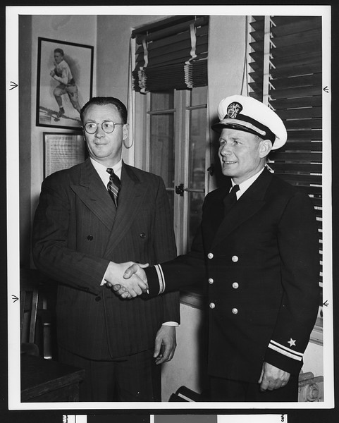 """University of Southern California football coach Jeff Cravath shaking hands with Roy """"Bullet"""" Baker, USC campus, 1944."""