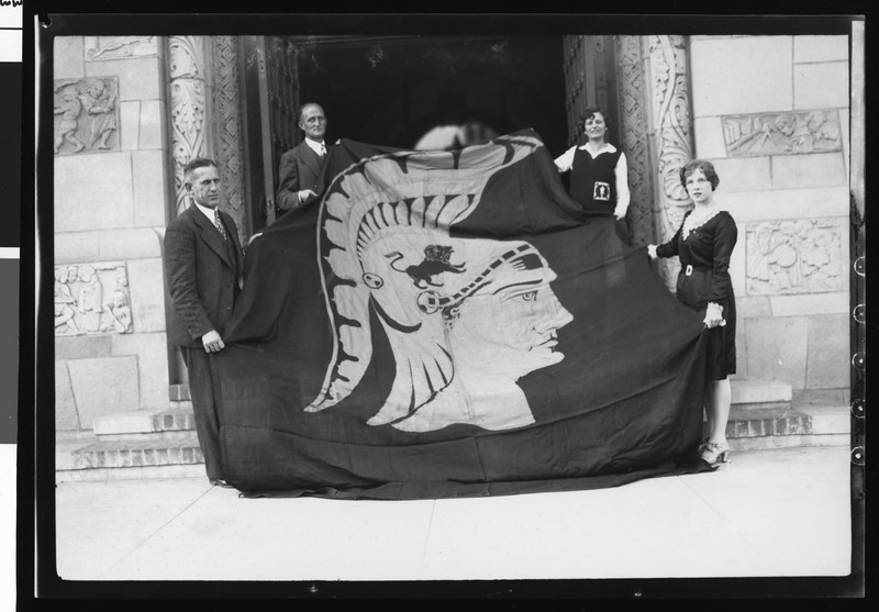 University of Southern California football coach Howard Jones and Bill Hunter holding the Trojan War Flag with two women, USC campus, 1928.