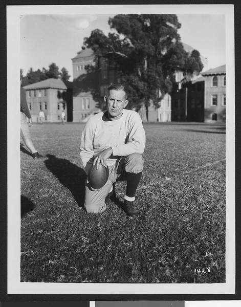 University of Southern California football coach Howard Jones, holding football on Bovard Field while on one knee, USC campus, 1933.