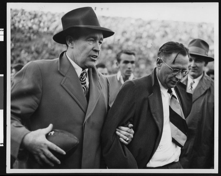 Notre Dame football coach Frank Leahy and University of Southern California football coach Jeff Cravath walking off the field together after game at Los Angeles Coliseum (waist high shots), 1947.