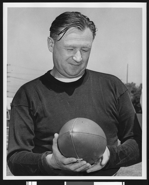 University of Southern California head football coach Jeff Cravath, shot to waist, dark sweatshirt, holding a football and looking at it. Bovard Field. 1949.