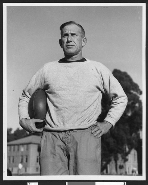 University of Southern California football coach Howard Jones holding football, hands on hips, Bovard Field, USC campus, 1933.