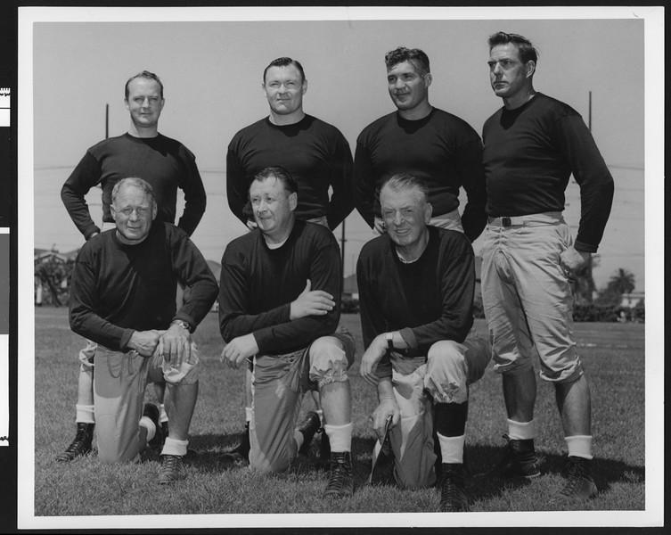 University of Southern California football coaching staff wearing dark sweatshirts, 1949, Bovard Field, USC campus.