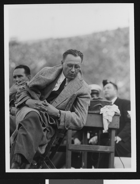 University of Southern California head football coach Jeff Cravath at the UCLA-USC game, long overcoat and leaning back in chair and looking down, Los Angeles Coliseum, 1944.
