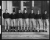 University of Southern California football 1950 coaching staff wearing dark sweatshirts and football pants, in front of the Physical Education building, USC campus.
