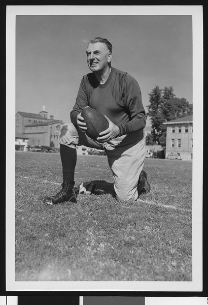 University of Southern California assistant football coach Sam Barry, in dark sweatshirt, kneeling and holding football, on Bovard Field, 1947.