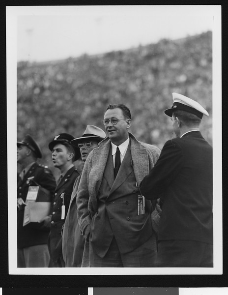 University of Southern California head football coach Jeff Cravath at the UCLA-USC game, hands in pockets, standing on sidelines, Los Angeles Coliseum, 1944.
