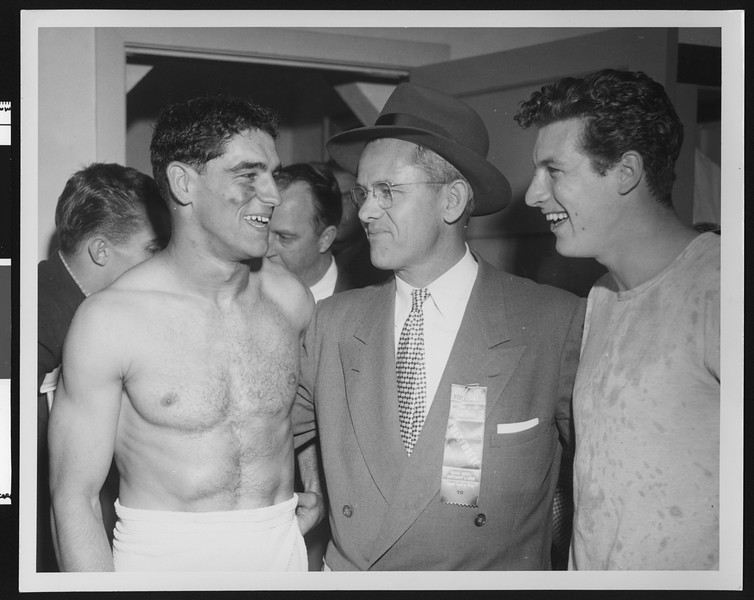 University of Southern California football coach Jess Hill celebrates 1953 Rose Bowl win with players in the locker room, Rose Bowl, 1953.