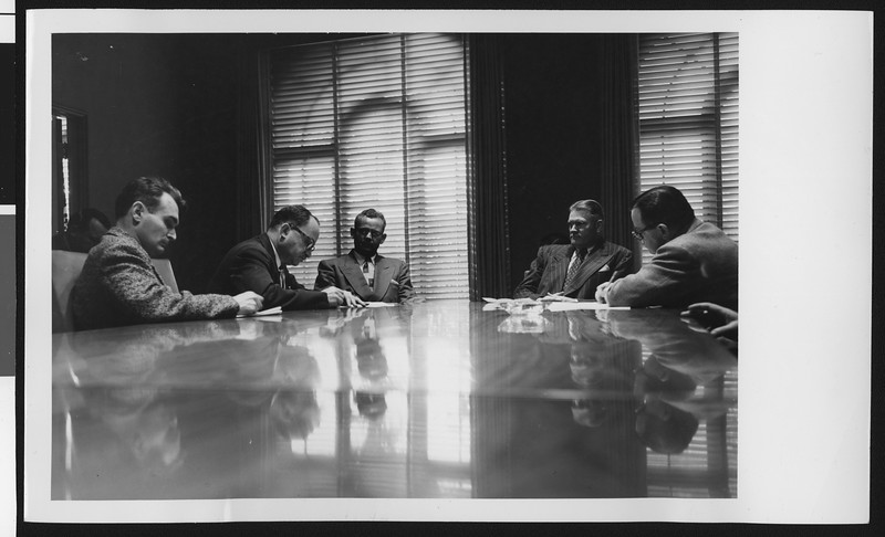 Press conference for new University of Southern California head football coach Jess Hill, with three reporters taking notes, January 1951.
