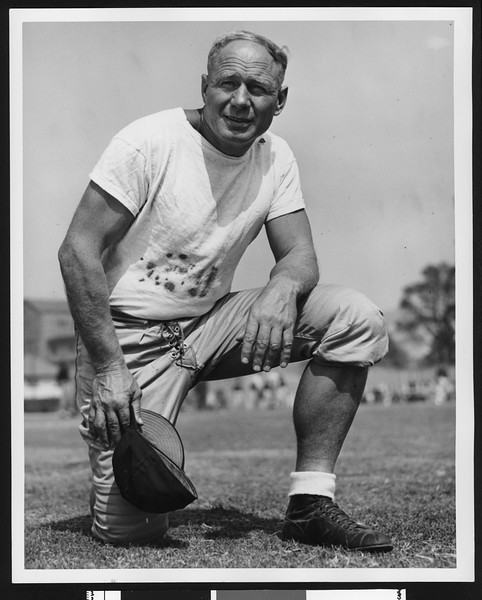 """University of Southern California assistant football coach Roy """"Bullet"""" Baker, on one knee, white tshirt, holding cap in hand, Bovard Field, 1946."""