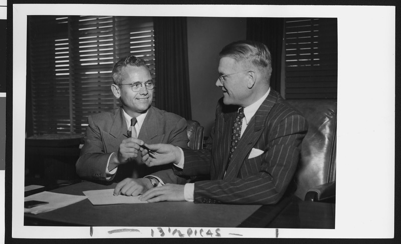 University of Southern California head football coach Jess Hill (left) takes a pen from President Fagg as they sign Hill's new football contract, USC campus, January 1951.