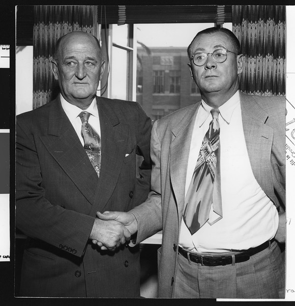 University of Southern California football coach Jeff Cravath shaking hands with Athletic Director Bill Hunter, probably after Cravath's resignation, USC campus, 1950.