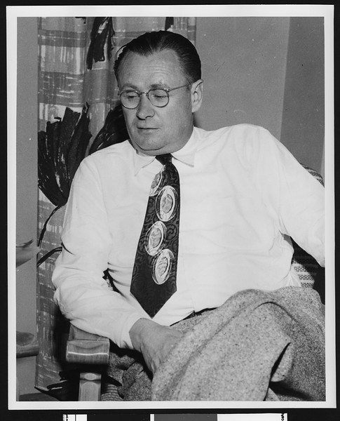 University of Southern California football coach Jeff Cravath sitting in chair wearing a tie with football shapes on it, Los Angeles, circa 1950.
