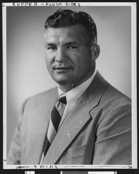 University of Southern California assistant football coach Ray George, studio shot, diagonally striped tie, grey jacket, 1949.
