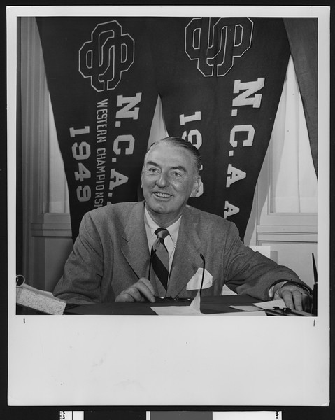University of Southern California sports coach Sam Barry in front of USC's NCAA championship banners, USC campus, 1950.