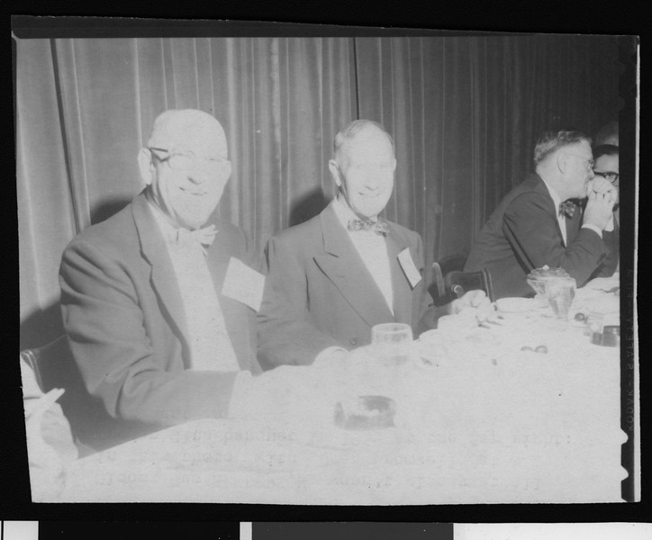 """Former University of Southern California head football coaches """"Gloomy Gus"""" Henderson and Dean Cromwell at a Trojan Club banquet, Los Angeles, 1955."""