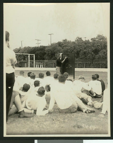 University of Southern California football coach Howard Jones at a football practice, diagramming a play on a chalkboard in front of the football team, Bovard Field, USC campus, 1929.
