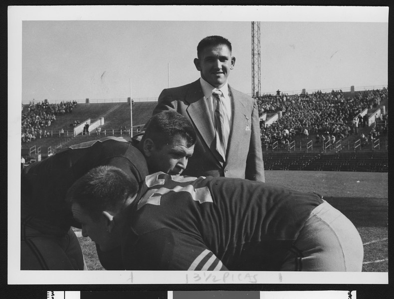 Navy football assistant coach Don Clark, wearing a suit, at pregame on Baltimore's Memorial Field with linebackers, 1950.