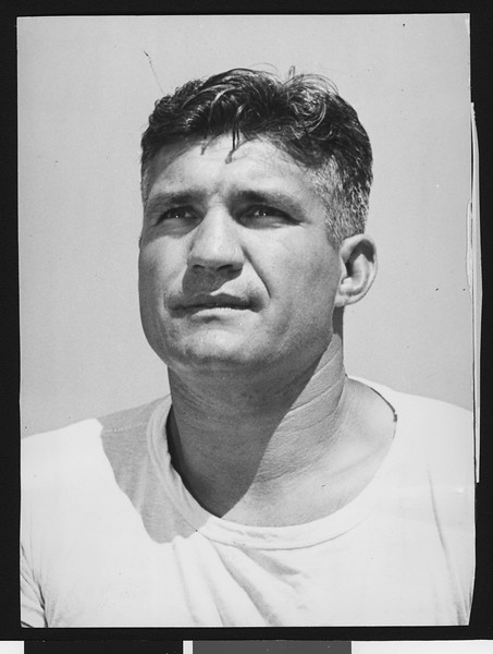 University of Southern California assistant football coach Ray George, wearing white t-shirt, chest high shot, 1946.
