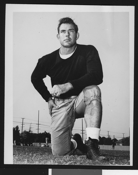 University of Southern California assistant football coach Bill Fisk, dark sweatshirt, on one knee, Bovard Field, 1949.