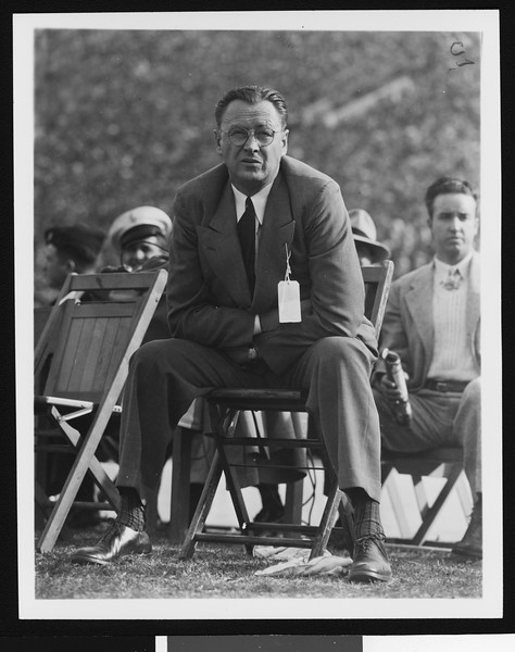 University of Southern California head football coach Jeff Cravath at the UCLA-USC game, sitting in a wooden chair on the sidelines clutching his sides, Los Angeles Coliseum, 1944.