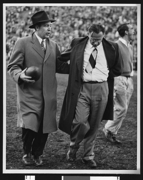 Notre Dame football coach Frank Leahy and University of Southern California football coach Jeff Cravath walking off the field together after game at Los Angeles Coliseum (full figure shots), 1947.