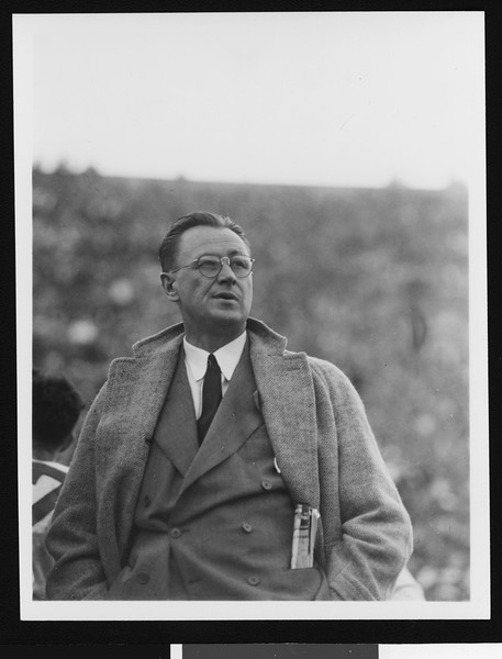 University of Southern California head football coach Jeff Cravath at the UCLA-USC game, hands in pockets, standing on sidelines, shot to waist, Los Angeles Coliseum, 1944.