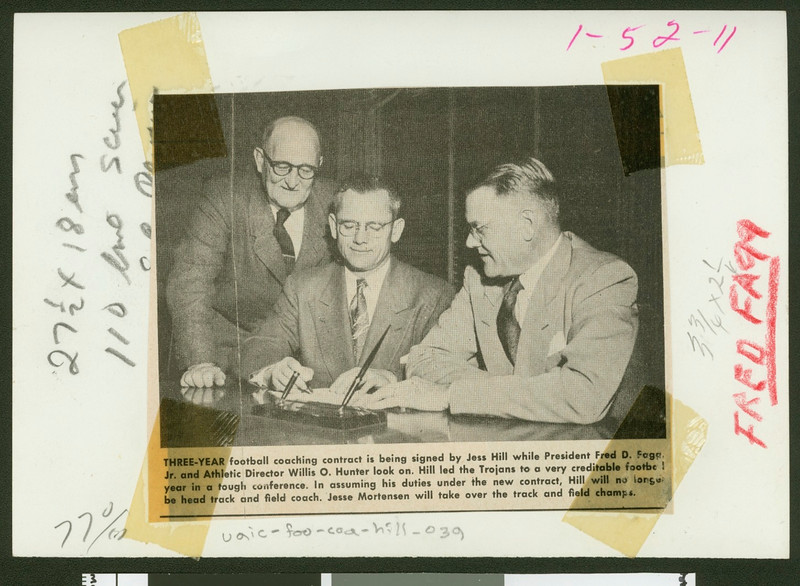 University of Southern California football coach Jess Hill signs a new three-year contract while Bill Hunter and President Fagg look on, USC campus, December 1951.