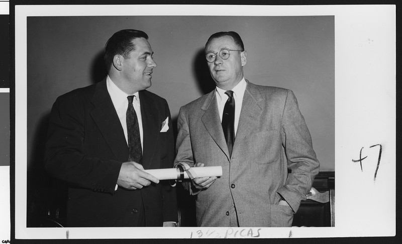 University of Southern California football coach Jeff Cravath receiving a scroll indicating lifetime membership in the Trojan Club from Eames Bishop, president of the Trojan Club, 1951.