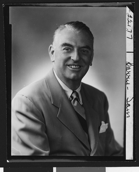 University of Southern California assistant football coach Sam Barry, posed in suit, striped tie, and handkerchief (smiling), 1949.