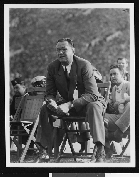 University of Southern California head football coach Jeff Cravath at the UCLA-USC game, sitting in a wooden chair on the sidelines holding a rolled up program, Los Angeles Coliseum, 1944.