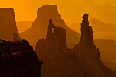 Sunrise through a wildfire haze Washerwoman Arch - shot through Mesa Arch