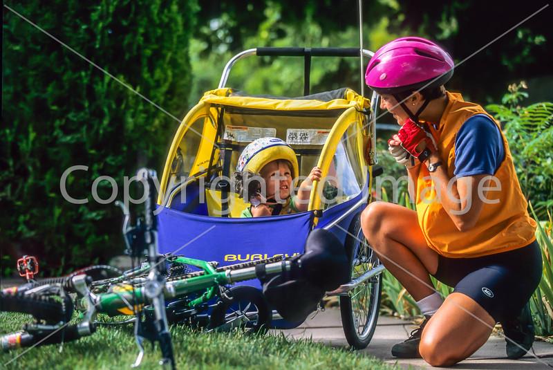 Mother with child in bike trailer - Liberty Park, Salt Lake City, Utah - 6-2 - 72 ppi