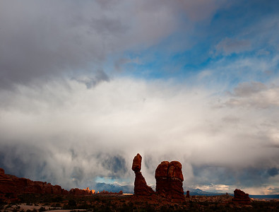Storm clouds over Balanced Rock, Arches National Park in sunset light. Utah
