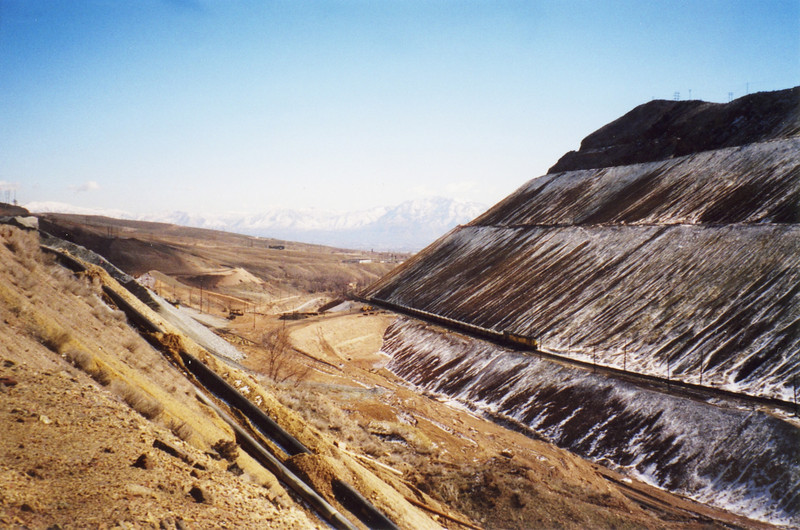 The last ore train from Bingham Canyon, on the right, passes the new Dry Fork reload site, on the left, about one mile above Copperton Yard. Note the new crossover track and fill that allows access from the lower transportation line (where the ore train is), over to the reload track. March 19, 2000.