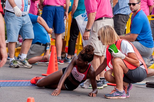 Iveen Chepkemoi collapses at the finish line after coming up just short in her bid to catch winner Caroline Rotich at the 2019 Boilermaker