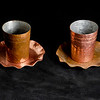 "<span id=""date"">_11/08/09_</span> <span id=""title"">Copper</span> When my family went through my late grandfather's house I claimed these copper cups, which are shotglass-sized. I'm not sure what the little platters are for, but there's 8 of them, and also 8 pint-size cups. There's also 2 trays, which apparently are ash trays. My grandfather probably picked them up when he was stationed in Chile during WWII. The following is stamped on the bottom of everything: ""Enrique Avalos, R M - Hand Made - Chile"" Anyone know what R M means? I spent a good portion of the day polishing them to what I assume is their former glory. It was a lot of work, and I didn't get to everything, as shown in this photo. I thought a polished and non-polished version would be an interesting juxtaposition. I positioned them on some black leather for the background and lit them from the side using a reflector on my flash unit.  <a href=""http://www.jawsnap.net/gallery/4429824_zbVM5#471999708_53d7K"">[last year]</a>"